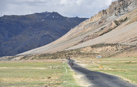 Biker riding at valley in mountains photo