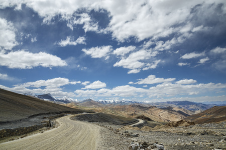 View of curved road among snow capped mountains photo