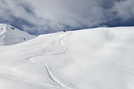 deep powder snow: Winding snowboard trail among virgin snow mountains Stock Photo