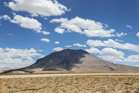 shadowed: Lonely mount shadowed by clouds Stock Photo