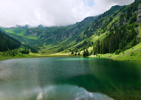 Alpine mountain lake among clouds and mountains summer landscape