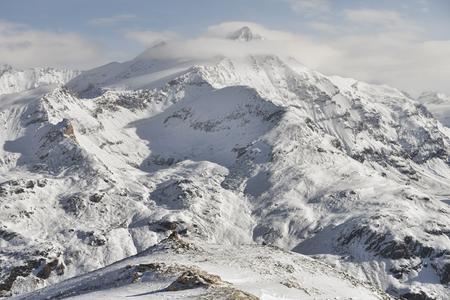 上にいくつかの雲と雪に覆われた高山のピーク 写真素材