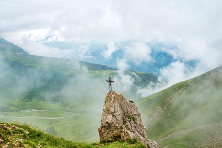 Metal cross monument at the top of rock in mountains Stock Photo