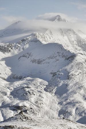 リモートの小さな男の雄大な山の背景付きフィギュア