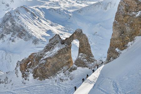 冬の高山の山斜面でハイカーのリモート グループ 写真素材