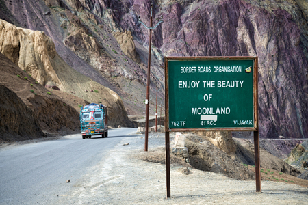 Moonland sign among mountain landscape and truck on road Stock Photo - 85672883