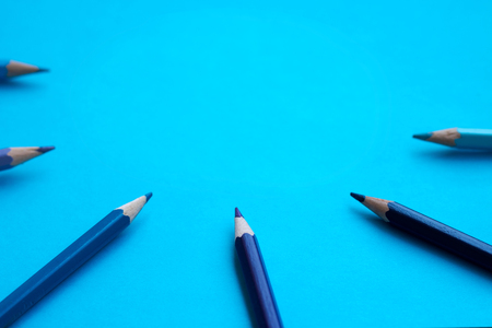 Blue colored pencils in a semicircle -  blue background Stock Photo