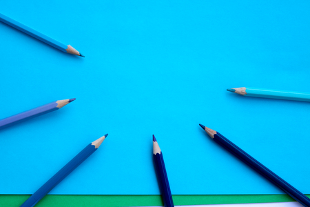 Colored pencils in shades of blue on blue background