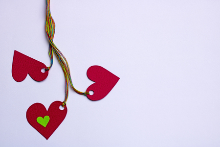 Three hearts linked colorful ropes - on white background, copy space