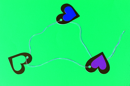 Three hearts in a triangle - love triangle, on green background