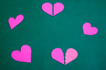 broken love: Pink - purple paper hearts on a green background, in a circle Stock Photo