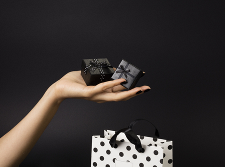 Female hand holding a three black gift-boxes on a palm, black gift-bag decorated with white polka dots below. Black background.
