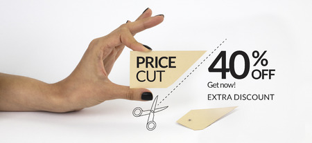 Female hand with black nails, holding scissors and cutting a price tag. Isolated on grey background.