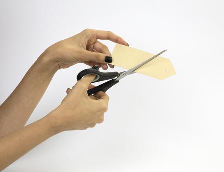 Weibliche Hand mit schwarzen Nägeln, halten Scheren und schneiden einen Preis. Getrennt auf grauem Hintergrund. Standard-Bild