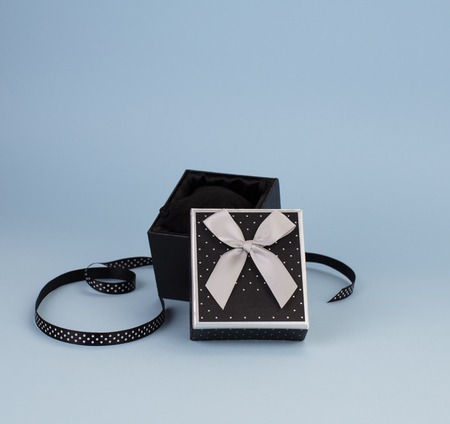 A black box, with an open lid; satin ribbon with polka dots next to it. Grey background.