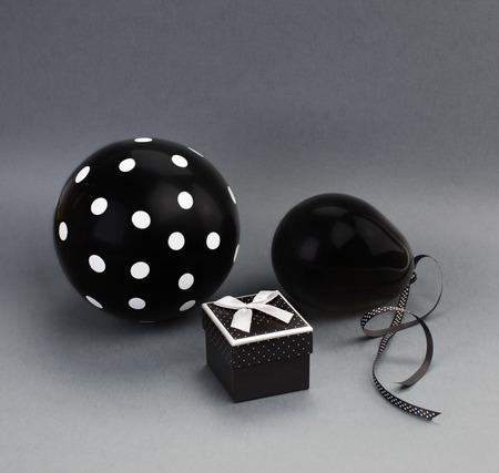 Two black balloons (one of them with white polka dots on it) and a black box with a grey satin bow on a lid. Grey background. 版權商用圖片