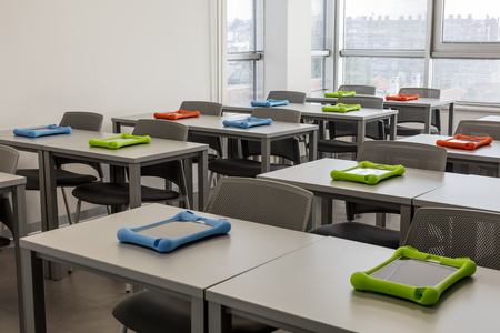 Modern classroom interior, with work desks and chairs; city view in the background 版權商用圖片