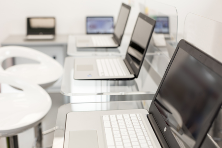 New, open laptops, on a glass desktop; modern white chairs in background.