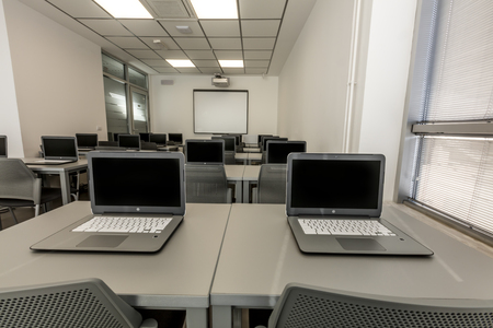 Modern office, work desks with laptops. In depth photography.