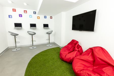 Modern waiting, or lounge room; laptops, TV and beanbags in the background.