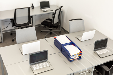 Modern office space, with desks and laptops.