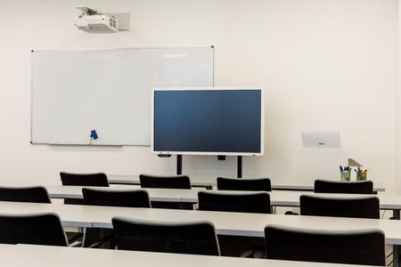Modern classroom interior, with white board, work desks and chairs. 版權商用圖片