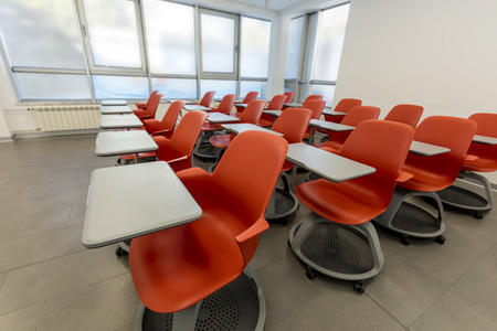 Modern classroom interior, with white board and movable tables and chairs. Theater style setting.