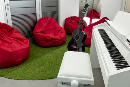 Modern music-room, with white piano and black guitar; red beanbags in the background.