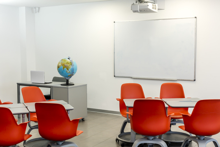 Modern classroom interior, with white board and movable tables and chairs. 版權商用圖片