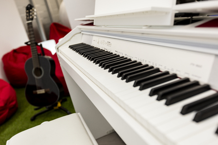 Modern, white piano keyboard in focus, black guitar and red beanbags in the background.