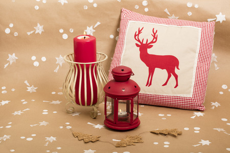 Christmas holiday composition, with candles and cushion with deer design.