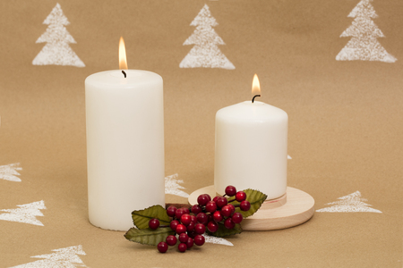 Christmas composition – white, lit candles with mistletoe berries.