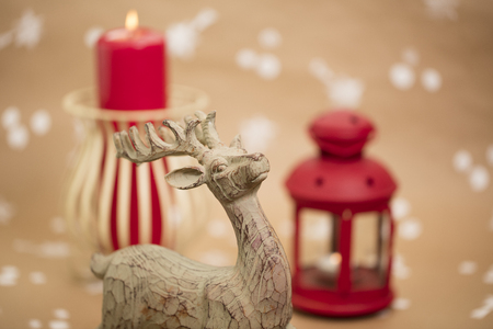 Christmas holiday composition, with candles and wooden deer figurine. 版權商用圖片