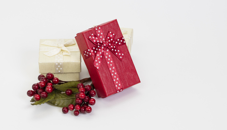 Christmas composition – white and red gift boxes, mistletoe berries on white background.