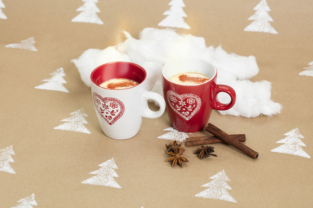 Christmas composition on handmade background – white & red mugs, cinnamon sticks and star anise beside.