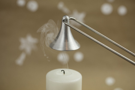 White candle, freshly extinguished. Silver candle snuffer. Christmas atmosphere.