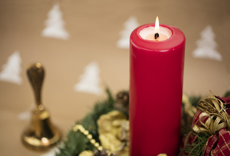 Christmas composition with yule wreath, golden ornaments and red candle.