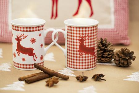 Christmas composition – mugs with deer motive, cinnamon sticks, anise and pinecones.