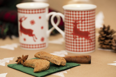 Christmas composition – mugs with deer motive, cookies, cinnamon sticks, anise, pinecones and plaid blanket. 版權商用圖片