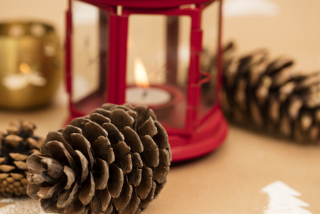 Christmas composition – pinecone, red lantern with lit candle in the background. 版權商用圖片