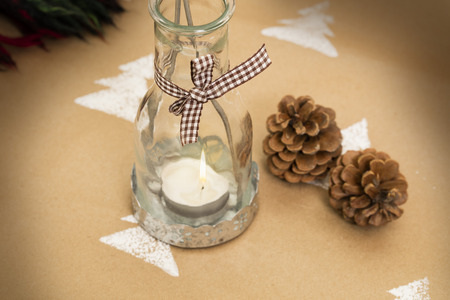 Winter composition - glass candle-holder with lit candle; pine-cones beside.