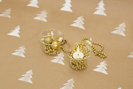Christmas composition – golden ornaments and lit candle in glass candle holders.