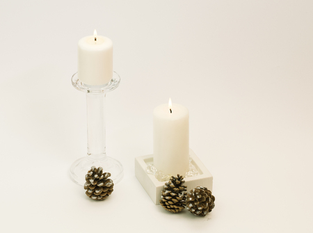 Winter composition – lit, white candles in glass and wooden candle-holders, pinecones beside. White background.
