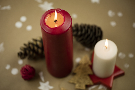 Christmas composition with candles, ornaments and pinecones, on handmade vintage background.