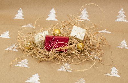 Christmas composition – gift boxes and gold ornaments on handmade background.