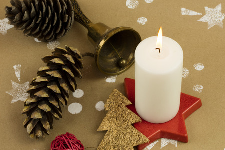 Christmas composition with candles, ornaments, brass bell, and pinecones, on handmade vintage background. 版權商用圖片