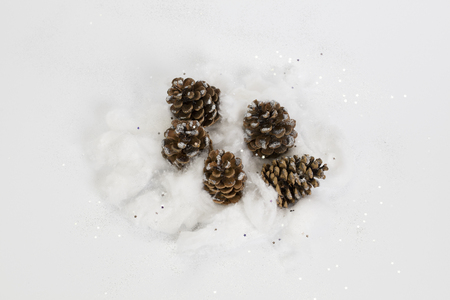 Winter composition – pinecones with silver sequins on white background.