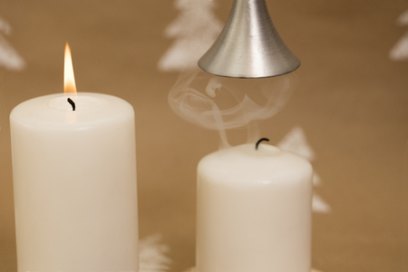 Christmas composition – white candles with mistletoe berries, with female hand holding candle snuffer.