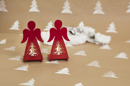 Christmas composition; red angel-shaped candle holders, with lit candles on handmade background.