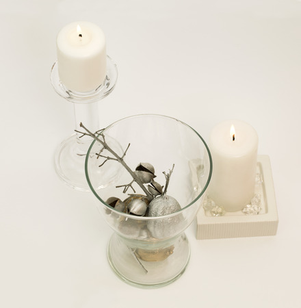 Winter composition – lit, white candle in glass candle-holder and silver decoration in glass vase. White background.